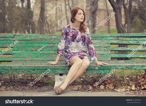 girl sitting on a bench style redhead girl sitting on bench stock photo 134009834