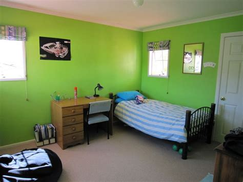 a simple 12 year old boys bedroom with blue striped bed and wooden cabinet also a bean bag in