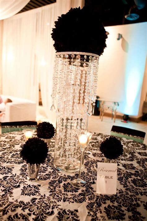 Black flower ball in giant cylinder vase with chandelier