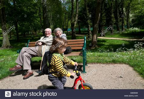 bench couple watch elderly couple on bench enjoying watching a little boy on his bike in stock photo