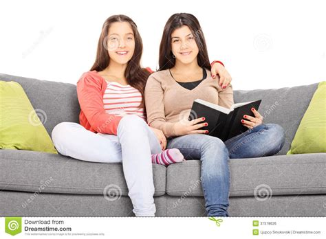 two girls having on the couch two girls seated on sofa hugging and looking at camera