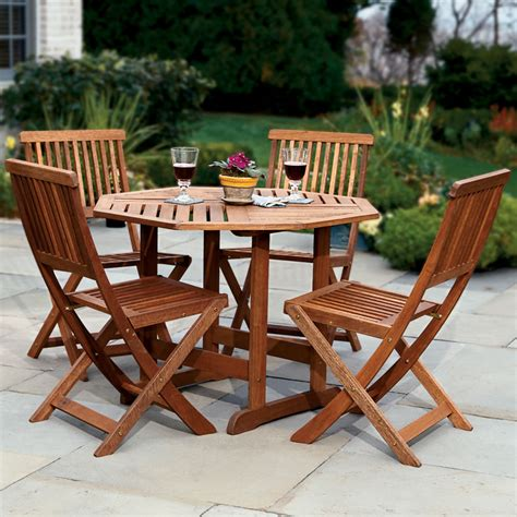 Outdoor Patio Tables The Trestle Patio Table And Stow Away Chairs Hammacher Schlemmer