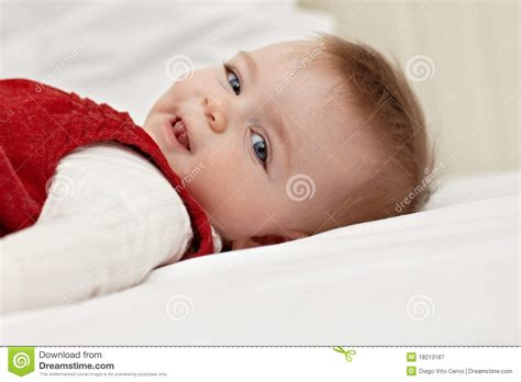 lying on bed little girl lying on bed and smiling royalty free stock