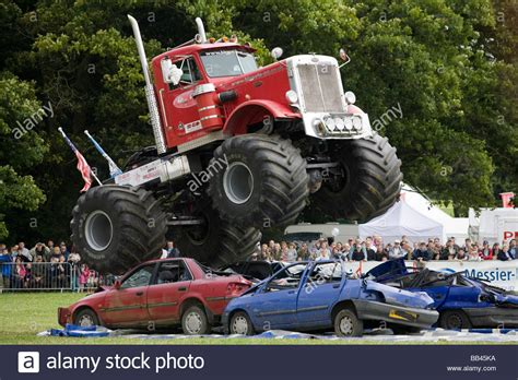 Monster Trucks Crushing Old Cars At A Farm Show