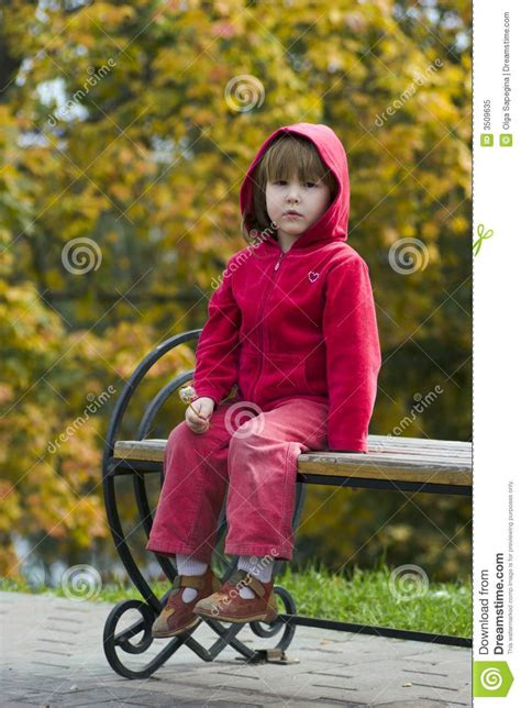 kid on bench kid sitting on bench outdoors royalty free stock photo