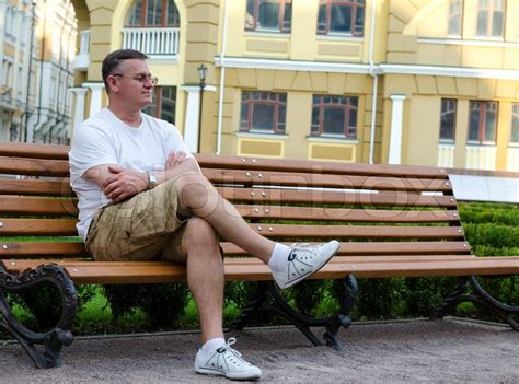 people sitting on bench man sitting waiting on an urban bench stock photo