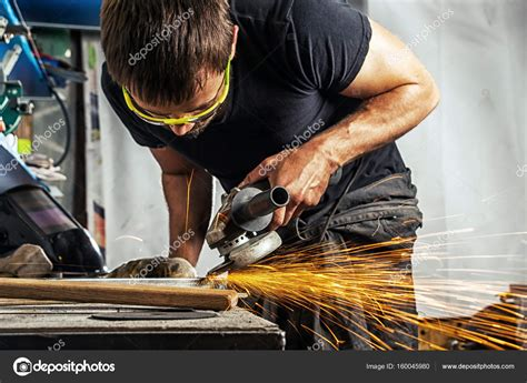 Man Grinding Metal With A Angle Grinder Stock Photo