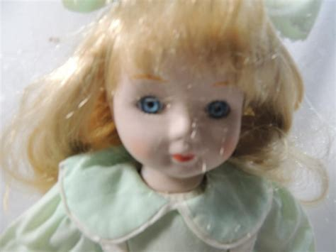 porcelain doll light porcelain doll in light green dress with stand