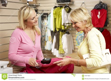 sales assistant with customer in clothing store stock