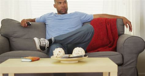 you sitting on the couch watching tv black man sitting on couch stock footage video 4784108