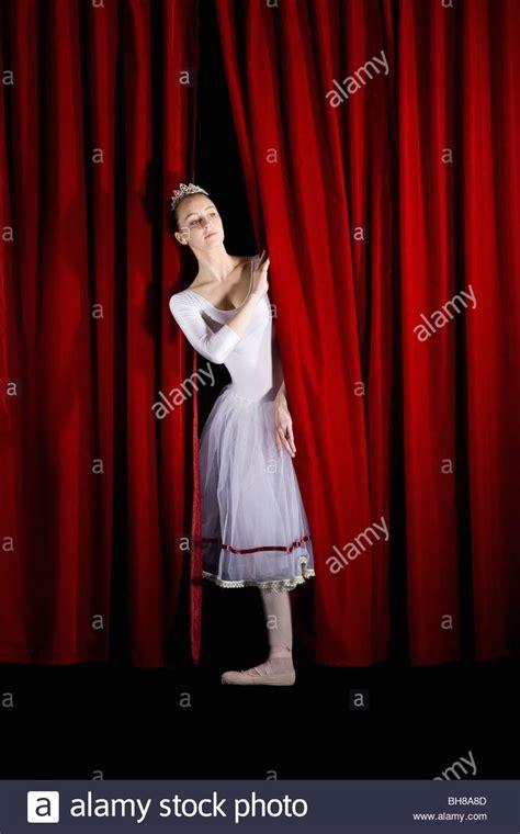 curtain dancers a ballet dancer peeking through a stage curtain front