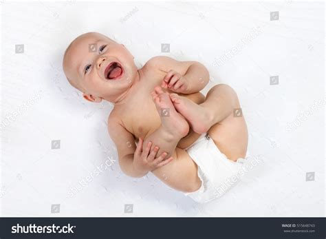 a small child in a nappy plays with the lock to a beach hut on the funny little baby wearing diaper playing stock photo
