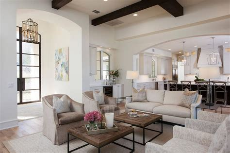 two living rooms side by side oatmeal linen sofa with side by side coffee tables transitional living room