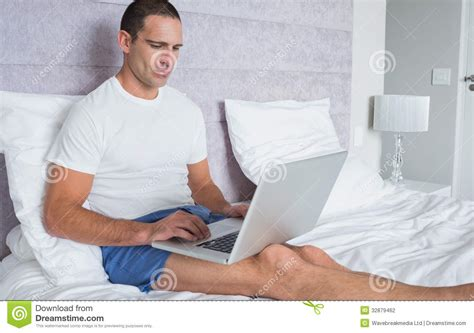 laptop in bed concentrating man using laptop on bed stock photography image 32879462