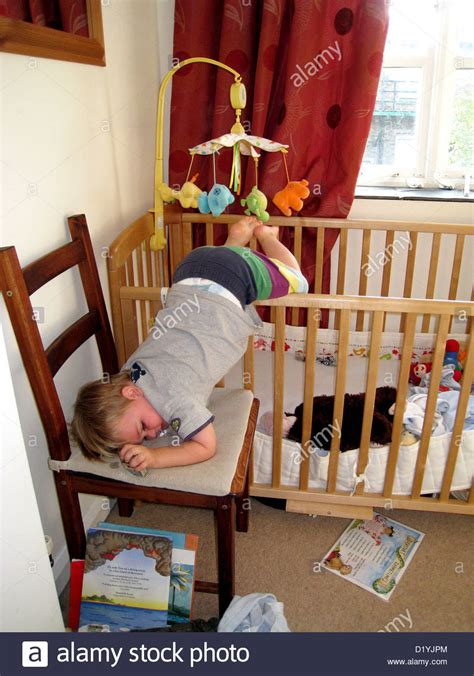 Baby Falls Out Of Crib Toddler Climbing Out Of Crib Onto A Chair Stock Photo