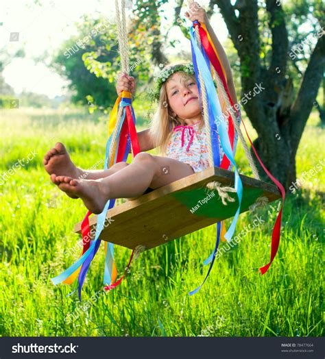 girl swinging on swing young cute girl on swing with ribbons in the garden stock