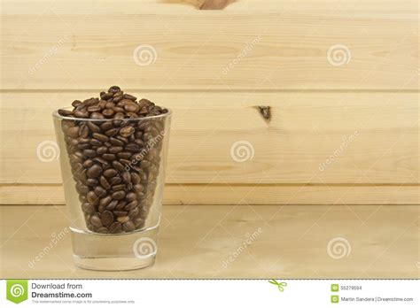 Shelf Of Beans by Glass With Coffee Beans Standing On A Wooden Shelf Stock