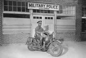 An african american military policeman on a motorcycle in front of the