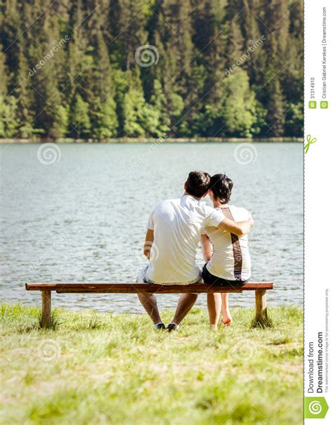 lovers bench young lovers sitting on wooden bench stock photo image