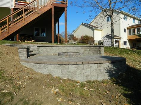 building a paver patio on a hill pit on hillside with retaining walls above and below