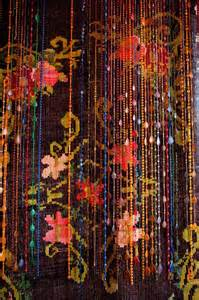 Beads hanging over a tapestry hippie beads beds beads bliss beads