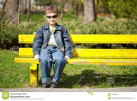 sitting on the bench cool kid sitting on bench royalty free stock images