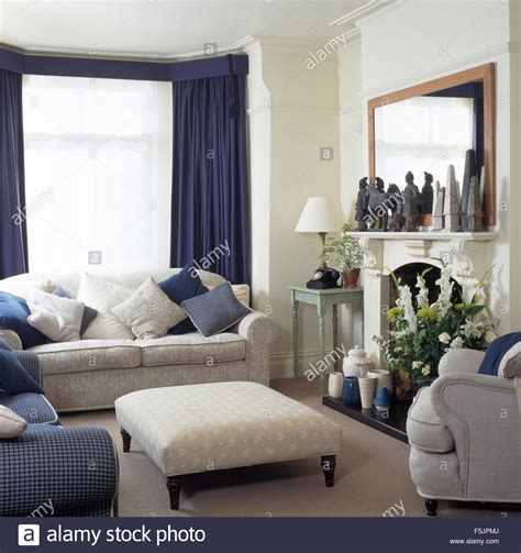 living room courtains sofa and ottoman stool in a townhouse living room with blue stock photo royalty free
