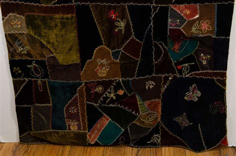 an antique handmade quilt in embroidered velvet at