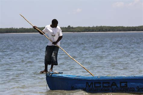 stick boat file flickr don macauley a man pushing a boat with a