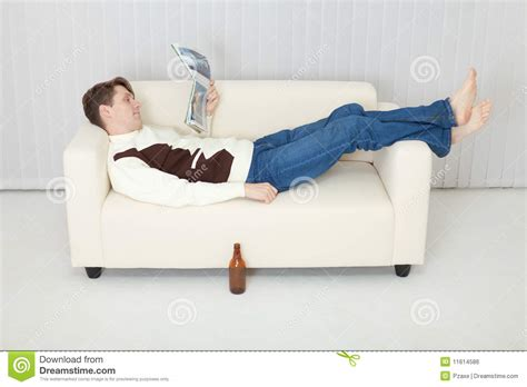 Lying On A Sofa by Person Comfortably Lie On Sofa With Journal Royalty Free