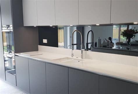 grey mirrored glass kitchen splashback complementing