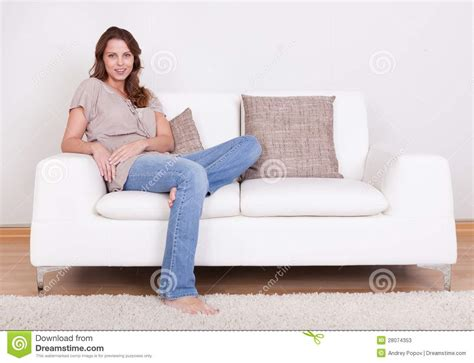 sitting in sofa casual woman sitting on a couch stock photos image 28074353