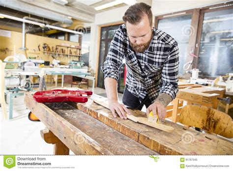 working man tattoo carpenter sanding a wooden guitar neck in workshop stock
