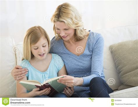 mom on sofa mother and daughter reading book together on sofa stock