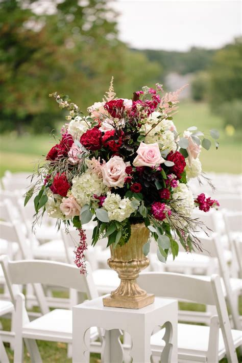 gold pedestal ceremony arrangement with pink roses and ranunculus ceremony spaces