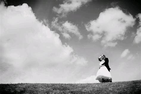 wallpaper black and white romantic bride and groom atop a hill hold each other with a