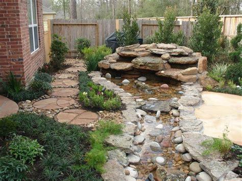 backyard creek landscaping with oversize pavers and backyard creek hkns