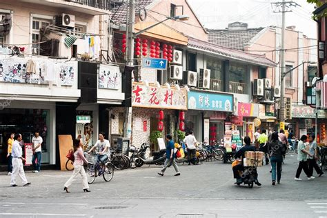 suburban people street of shanghai china with shops and people stock