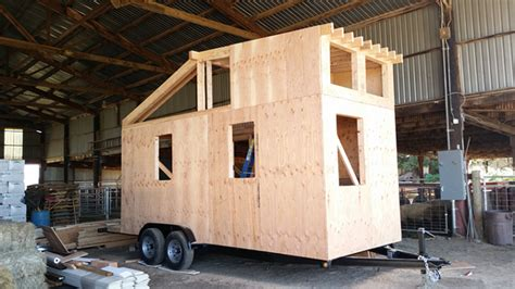 small home construction angels in toolbelts gather to build tiny house for