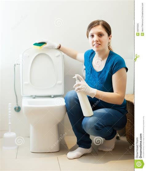 women in the bathroom woman in bathroom with sponge and cleaner royalty free