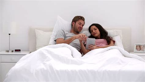 lovely couple in bed lying in bedroom affectionate couple lying on bed together in bedroom stock