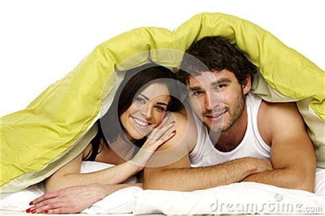 laid in bed beautiful couple in bed under a green duvet royalty free