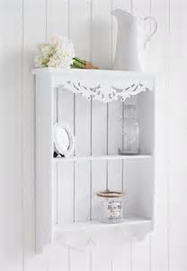 white wall shelf with pegs for hanging