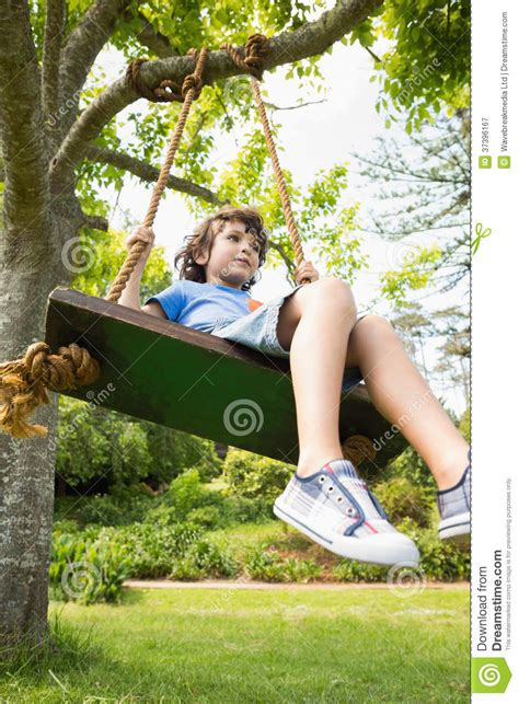 young swing low angle view of a cute little boy on swing stock image