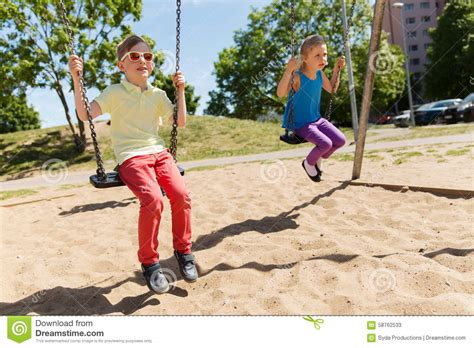 swinging with two happy kids swinging on swing at playground stock image