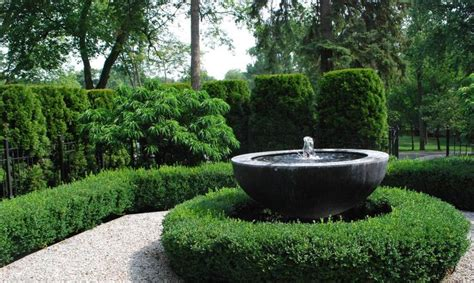 stone bowl water feature fountain surrounded  clipped