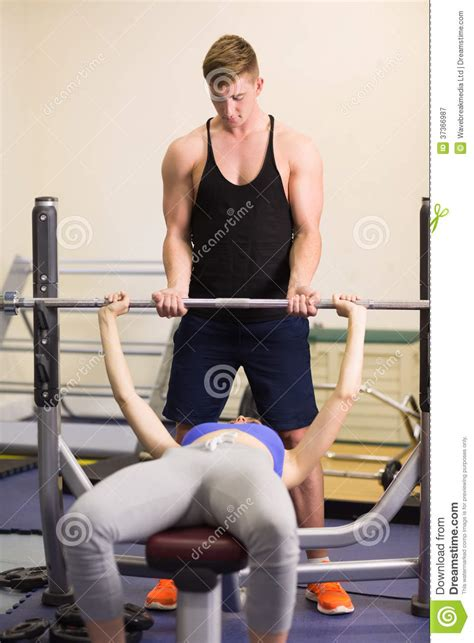 women bench pressing trainer helping woman to lift the barbell bench press in gym royalty free stock