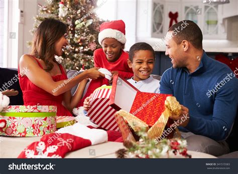 family opening christmas presents home together stock