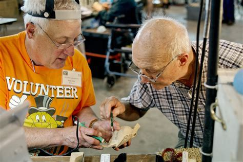 Craftsmen carve custom wood walking sticks for Veterans