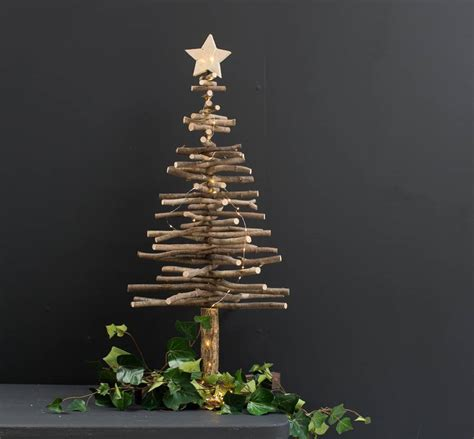 large wooden star topped tree by the forest co